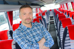 Uomo del ritratto stato in bus vuoto della navata laterale fotografia stock