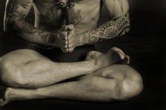 Uomo del tatuaggio che fa yoga immagine stock libera da diritti