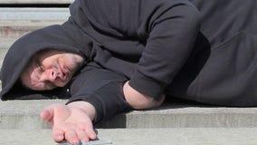 Uomo del tossicomane che dorme con la siringa vicino alla mano video d archivio