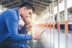 Uomo del viaggiatore che per mezzo del treno aspettante del telefono e della compressa sullo sta Immagini Stock