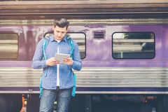 Uomo del viaggiatore che per mezzo del treno aspettante del telefono e della compressa sullo sta Fotografia Stock