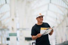 Uomo del viaggiatore con bagaglio e mappa nella stazione ferroviaria concetto di corsa immagini stock libere da diritti