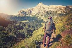 Uomo del viaggiatore con il concetto di stile di vita di viaggio di alpinismo dello zaino Immagine Stock