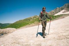 Uomo del viaggiatore con il ghiacciaio di alpinismo dello zaino Fotografie Stock