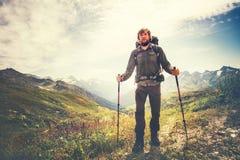 Uomo del viaggiatore con lo zaino e l'alpinismo dei pali di trekking Fotografia Stock Libera da Diritti