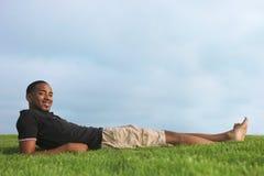 Uomo dell'afroamericano che riposa nell'erba verde Fotografie Stock Libere da Diritti