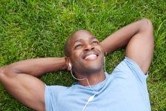 Uomo dell'afroamericano che si trova nell'erba Immagine Stock