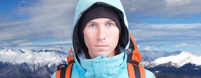 Uomo dell'alpinista che esamina la macchina fotografica, nelle alte montagne del fondo Ritratto del primo piano Immagine Stock