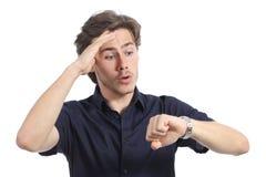 Uomo dell'ansioso che esaurisce tempo che guarda il suo orologio Immagini Stock