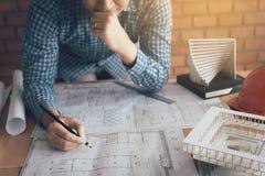 Uomo dell'architetto che guarda modello sullo scrittorio con lo sforzo circa proble Fotografia Stock Libera da Diritti