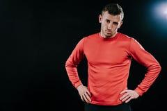 Uomo dell'atleta in abiti sportivi rossi che controlla fondo scuro, tenentesi per mano sul suo stile di vita della vita, sport, m Fotografia Stock Libera da Diritti