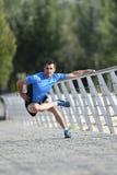 Uomo dell'atleta che allunga le gambe che si scaldano i muscoli prima dell'allenamento corrente che si appoggia il parco urbano d Fotografie Stock Libere da Diritti