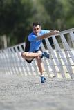 Uomo dell'atleta che allunga le gambe che si scaldano i muscoli prima dell'allenamento corrente che si appoggia il parco urbano d Fotografia Stock