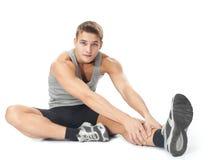 Uomo dell'atleta che fa gli esercizi di allungamenti Fotografie Stock Libere da Diritti
