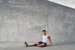 Uomo dell'atleta di forma fisica che si rilassa e che allunga i muscoli e le gambe Fotografie Stock