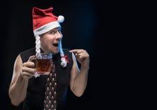 Uomo dell'attore comico in cappuccio con le trecce con un vetro di birra, in attesa del Natale e del nuovo anno Fotografia Stock