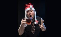 Uomo dell'attore comico in cappuccio con le trecce con un vetro di birra, in attesa del Natale e del nuovo anno Immagine Stock