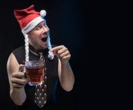Uomo dell'attore comico in cappuccio con le trecce con un vetro di birra, in attesa del Natale e del nuovo anno immagine stock libera da diritti