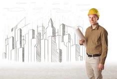 Uomo dell'ingegnere con la città della costruzione che assorbe fondo Fotografie Stock