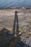 Uomo dell'ombra in una roccia della riva di mare immagini stock libere da diritti