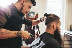 Uomo della barba che ottiene taglio di capelli al salone immagine stock libera da diritti