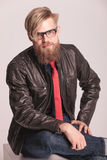 Uomo della barba che si siede e che sorride alla macchina fotografica Fotografie Stock