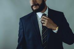 Uomo della barba nei sorrisetti di un vestito del blu immagine stock libera da diritti