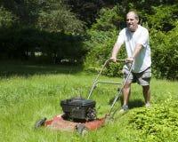 uomo della casa dell'erba di taglio suburbano Fotografia Stock Libera da Diritti