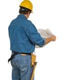 Uomo della costruzione che esamina i programmi della costruzione fotografia stock libera da diritti