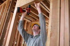 Uomo della costruzione che per mezzo del trivello Fotografia Stock