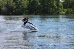 Uomo della foto di azione sul jet ski salto Fotografia Stock