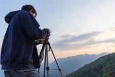 Uomo della macchina fotografica che prende foto sulla montagna Fotografia Stock Libera da Diritti