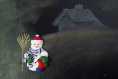 Uomo della neve con la sua scopa davanti alla casa fotografie stock