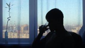 Uomo della siluetta, bevande al fondo della finestra archivi video