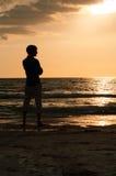 Uomo della siluetta che esamina fuori la spiaggia durante il tramonto Fotografie Stock Libere da Diritti