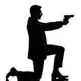 Uomo della siluetta che si inginocchia mirando pistola Immagini Stock