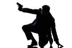Uomo della siluetta che si inginocchia mirando pistola Fotografie Stock