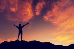 Uomo della siluetta che sta sul fondo di tramonto della montagna immagini stock libere da diritti