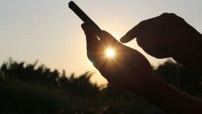 Uomo della siluetta facendo uso di Smartphone sul tramonto