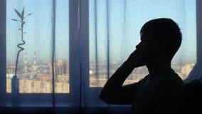Uomo della siluetta, parlante al fondo della finestra stock footage