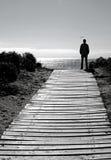 Uomo della siluetta sul percorso della spiaggia Fotografie Stock