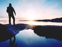 Uomo della siluetta sulla scogliera sopra il mare Supporto turistico da solo sull'orizzonte di mare dell'orologio e della roccia immagini stock