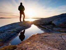 Uomo della siluetta sulla scogliera sopra il mare Supporto turistico da solo sull'orizzonte di mare dell'orologio e della roccia fotografie stock