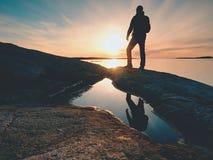 Uomo della siluetta sulla scogliera sopra il mare Supporto turistico da solo sull'orizzonte di mare dell'orologio e della roccia fotografia stock libera da diritti