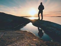 Uomo della siluetta sulla scogliera sopra il mare Supporto turistico da solo sull'orizzonte di mare dell'orologio e della roccia immagine stock libera da diritti