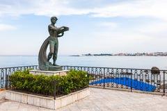 Uomo della statua ed il mare nella città di Giardini Naxos Immagine Stock