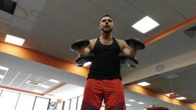Uomo della testa di legno al sollevamento pesi di forma fisica del bicipite di allenamento della palestra video d archivio