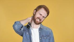 Uomo della testarossa con dolore al collo, fondo giallo stock footage
