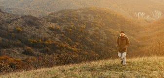 Uomo della viandante che cammina in montagne di autunno Fotografia Stock