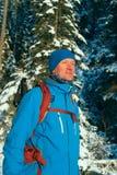 Uomo della viandante che sta nel legno di inverno sui precedenti di neve Immagine Stock